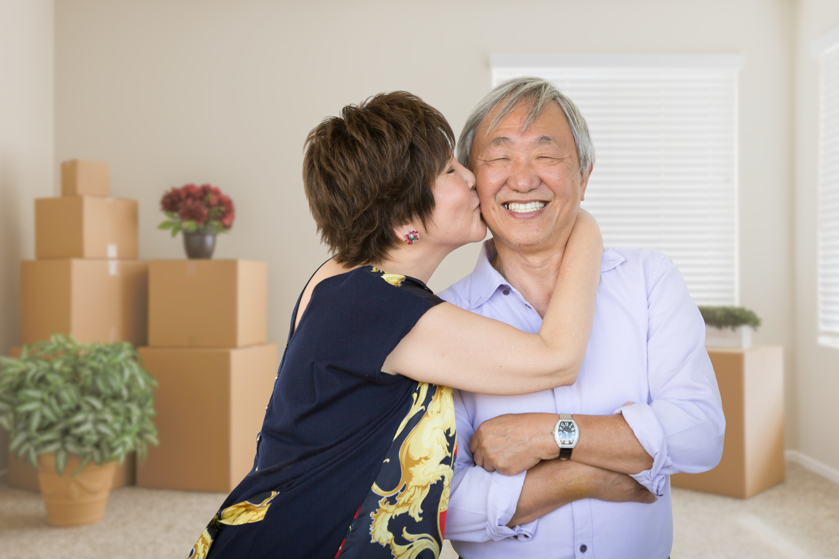 Happy Senior Chinese Couple Inside Empty Room with Moving Boxes and Plants.