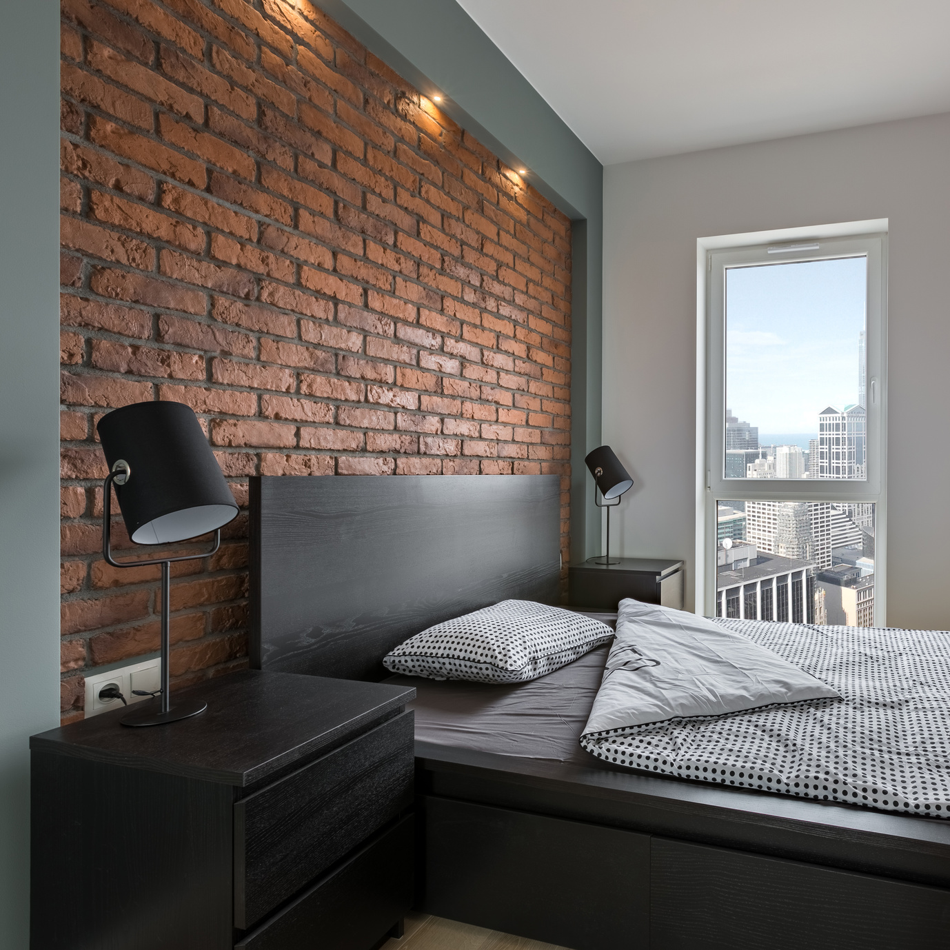 Industrial style bedroom with red, brick wall and double bed