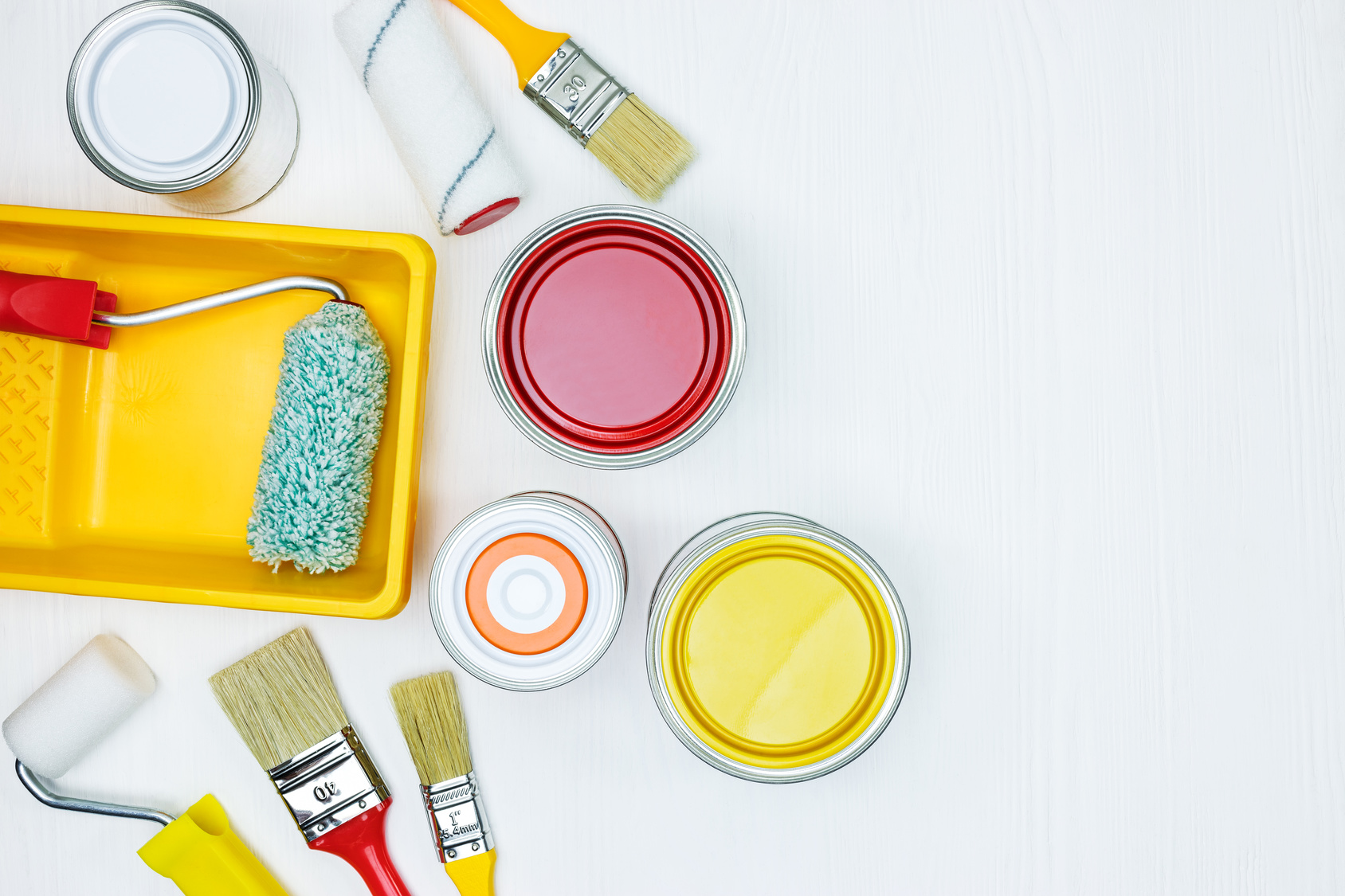 painting tools on white wooden background. paintbrushes, rollers, tray, cans with red, yellow, orange paint. flat view
